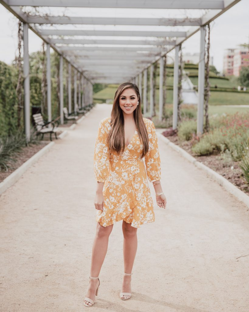 Casual look. Blogger is wearing a mustard yellow floral wrap dress. The dress length is above the knee. The bottom hem is ruffled and 3/4 sleeves cover the shoulders. Great dress for a casual Easter. See more at thefashionablemaven.com