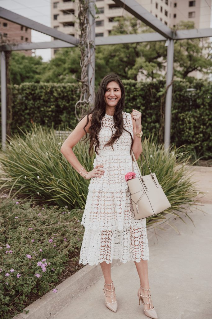 The blogger Jenni is wearing an elegant sleeveless crochet dress in white. Nude pumps with stud embellishments. Valentino rock stud dupe shoes.