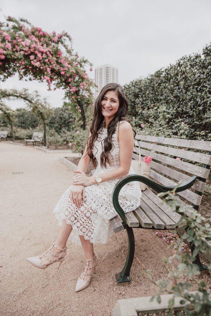 Blogger is modeling a white lace dress while sitting on a bench in the park. Three tiered skirt with nude sheer lining. 5 other Easter dress options.