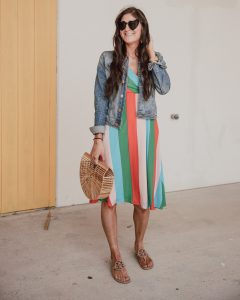 Jenni Metz is wearing a cute striped dress outfit with Tory Burch sandals and a denim jacket.