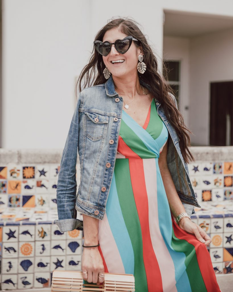 Jenni Metz- The Fashionable Maven is wearing a colorful striped dress, denim jacket, Tory Burch sandals, heart sunglasses, and bamboo bag. Click to see more striped dress outfits.
